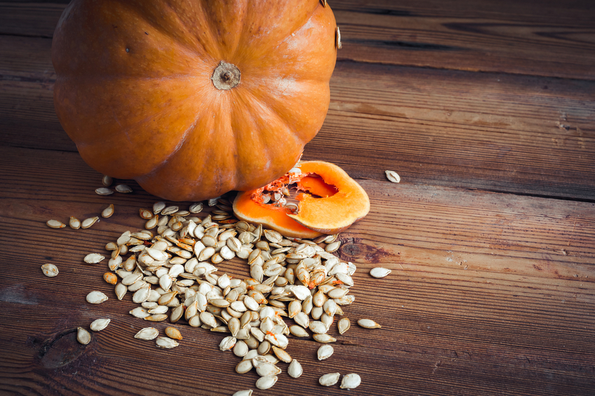 A pumpkin and seeds on a dark wood table